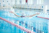 Girl swimming in butterfly stroke style — Stock Photo