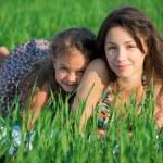 Happy girls lying on green grass — Stock Photo #52935671