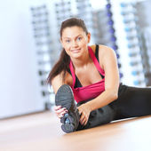 Woman doing stretching exercises at gym — Stockfoto
