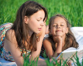 Girls reading book on green grass — Stock Photo