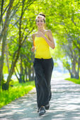 Woman running outdoors in green park — Stock Photo