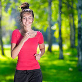 Woman running outdoors in green park — Stockfoto