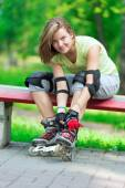 Girl putting on inline skates on bench — Stock Photo