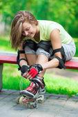 Girl putting on inline skates on bench — Stock Photo