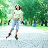 Sporty girl in park on inline skate — Stok fotoğraf