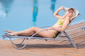 Young woman in swimsuit laying on chaise-longue — 图库照片