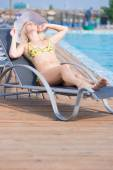 Woman in swimsuit laying on chaise-longue — Stock Photo