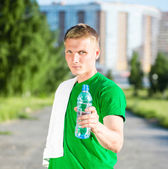 Tired man with white towel drinking water from a plastic bottle — Stock Photo