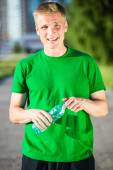 Tired man drinking water from a plastic bottle after fitness — Stock Photo