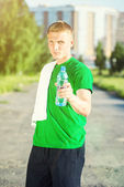 Trött man med vit handduk dricksvatten — Stockfoto