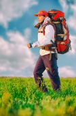 Hiker with backpack walking in the field — Stock Photo