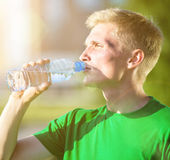 Tired man drinking water after fitness — Stock Photo