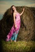 Woman standing in evening field over haystack. — Stock Photo