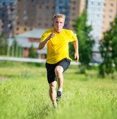 Sporty man jogging in city street park — Stock Photo