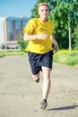 Sporty man jogging in city street park. — Stock Photo