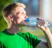 Tired man drinking water from a plastic bottle after fitness — Stockfoto
