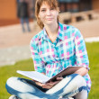 Student girl with copybook on bench. Summer campus park. — Stock Photo #69529311