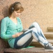 Beautiful young woman student with note pad and headphones. Outdoor student. — Stock Photo #69529873