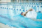 Young girl in goggles swimming front crawl stroke style — Stock Photo