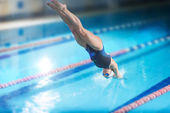 Female swimmer, that jumping into indoor swimming pool. — ストック写真