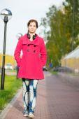 Beautiful woman in red coat walking autumn street. — Stock Photo