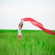 Young lady runing with tissue in green field. Woman with scarf. — Stock Photo #70133959