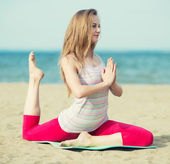 Young lady practicing yoga. Workout near ocean sea coast. — Stock Photo
