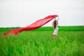 Young lady runing with tissue in green field. Woman with scarf. — Stock Photo