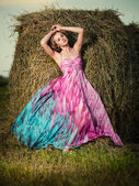 Young woman standing in evening field over haystack. Fashion sty — Stock Photo