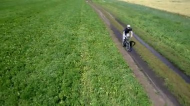 Man cycling on a rural road. Aerial view. — Stock Video