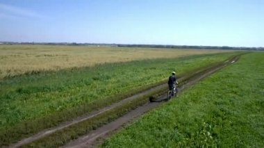 Man cycling on a rural road. Aerial view. — Vídeo stock