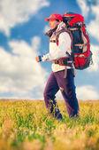 Wandelaar met rugzak wandelen in het veld — Stockfoto