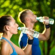 Man and woman drinking water from bottle after fitness sport exercise — Stock Photo #72594727