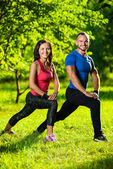 Man and woman doing stretching exercises — Стоковое фото