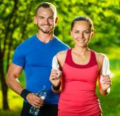 Athletic man and woman after fitness exercise — Stock Photo
