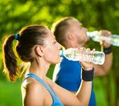 Man and woman drinking water from bottle after fitness sport exercise — Stock Photo