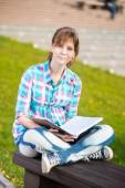 Student girl with copybook on bench. Summer campus park. — Stock Photo