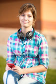 Smiling young college girl texting on a cell phone. Campus — Stockfoto