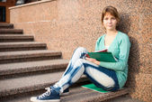 Girl sitting on stairs and reading note — Stock Photo