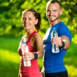 Man and woman drinking water from bottle after fitness sport exercise — Stock Photo #74787659