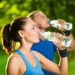 Man and woman drinking water from bottle after fitness sport exercise — Stock Photo #74787753