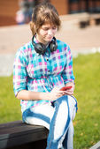 Smiling young college girl texting on a cell phone. Campus — Stock Photo
