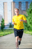 Sporty man jogging in city street park. Outdoor fitness. — Stock Photo