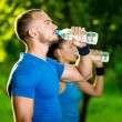 Man and woman drinking water from bottle after fitness sport exercise — Stock Photo #77005699