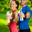 Man and woman drinking water from bottle after fitness sport exercise — Stock Photo #77009275