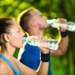 Man and woman drinking water from bottle after fitness sport exercise — Stock Photo #77009517
