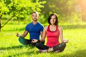 Genç adam ve kadın güneşli yaz parkta yoga yaparken — Stok fotoğraf