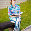 Student girl with copybook on bench. Summer campus park. — Stock Photo #77011455