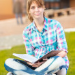 Student girl with copybook on bench. Summer campus park. — Stock Photo #77011725