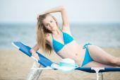 Młoda dama opalając się na plaży. Piękna kobieta pozowanie w — Zdjęcie stockowe